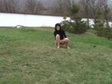 La jeune brunette pisse dans un parc